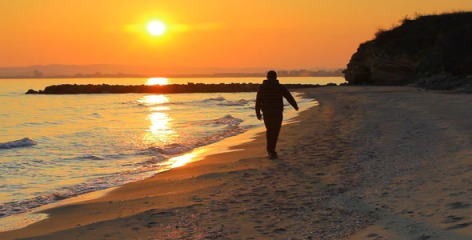 Man walks along beach at sunset